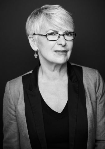 Black and white studio photograph of an older woman. She has very short gray hair, and she wears earrings, glasses, a black blouse, and gray and black jacket. She smiles discreetly at the camera.