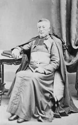 Photographie en noir et blanc d'un homme d'un certain âge portant les vêtements liturgiques d'un évêque. Il ne porte pas la calotte. Il est assis sur une chaise, son bras droit appuyé sur une table, la main posée sur des livres. Il affiche un air sérieux.