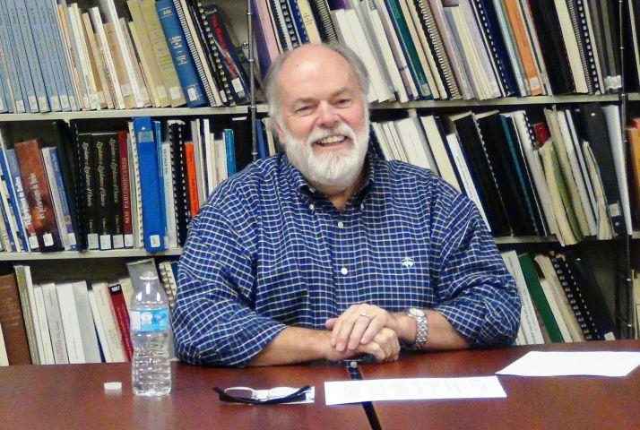 Photographie en couleur d'un homme d'âge mûr, portant la barbe. Vêtu d'une chemise carreautée, il sourit à la caméra. Il est assis à une table. Derrière lui, une bibliothèque.