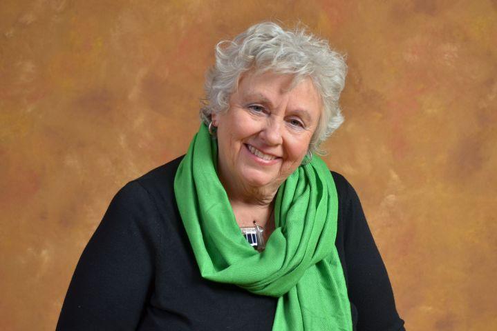 Photographie en couleur d'une femme d'âge mûr, aux cheveux  bouclés. Elle porte une veste noire et a une écharpe verte nouée autour du cou. Elle arbore un sourire.