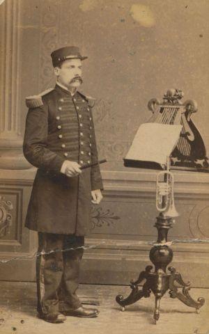 Photographie sépia d'un homme d'âge moyen. Il porte un uniforme et est debout devant un lutrin richement sculpté où reposent des partitions de musique et une trompette. Le nom et le titre du sujet sont écrits à la main au bas de la photo.