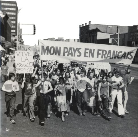 """Black and white photograph of a group of young people protesting in the street. Individual at the front carry a banner reading """"Mon pays en français"""" and a placard reading """"Vive la francophonie""""."""