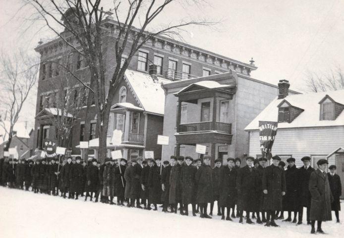 Photographie en noir et blanc d'une colonne d'une cinquantaine de jeunes, habillés pour l'hiver. Ils brandissent des pancartes et des banderoles qui contiennent des messages, tels « Pay our Teachers » et « British Fair Play ». À l'arrière-plan,  un édifice de brique de trois étages et trois maisons.