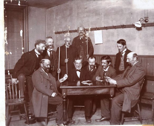 Black and white photograph of a group of men around a table. Five men are seated. Five others, including one cleric, are standing, some holding billiard cues. Two of the seated men hold cards in their hands. The photograph is slightly damaged.