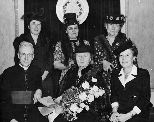 Black and white photograph of a group of women of various ages, wearing hats and dresses and fur stoles, except for one. Two women are seated, and one holds a bouquet of flowers. A priest is seated to their right. Three other women are standing behind them.