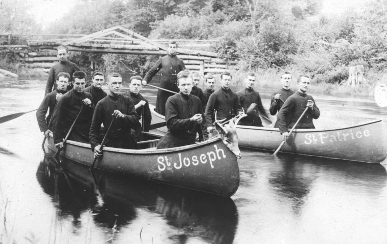 Black and white photograph of fourteen seminarians paddling on a river. They are distributed between two canoes, whose names – St Joseph and St Patrice – are painted in white on the front of the boat. The canoes are pulling away from a small wooden bridge.