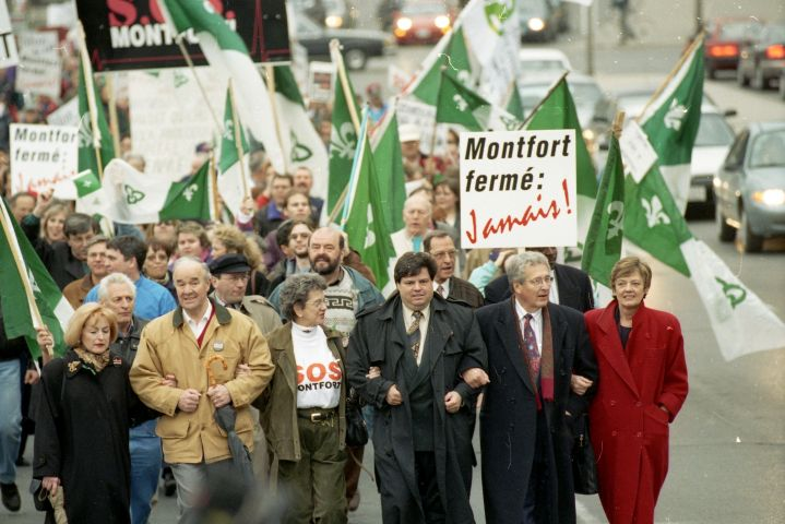 "Colour photograph of a large crowd walking down a city street, demonstrating. They are carrying Franco-Ontarian flags and placards that read, ""Montfort fermé : Jamais !"" with the ""Jamais"" positioned obliquely, in stylized red letters. The six people at the front of the crowd – three men and three women, most of them older – walk with their arms linked."