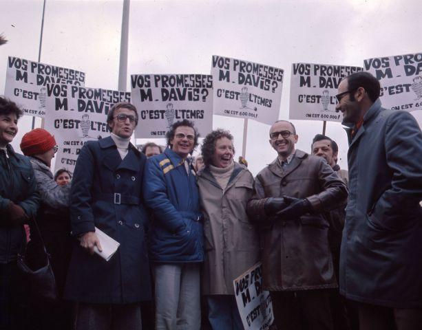 "Colour photograph of five middle-aged people – four men and a woman – in front of a group of demonstrators. They smile and hold placards which read, ""Vos promesses, M. Davis ? C'est l'temps. On est 600 000 !"" (Your promises, Mr. Davis? It's time. There are 600,000 of us!)."