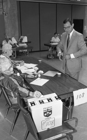 Black and white photograph of a mature, dark-haired man wearing glasses, and a suit and tie. He is standing in front of a polling station run by two elderly women. One of them is inserting a ballot into the ballot box. In the background, other polling stations.