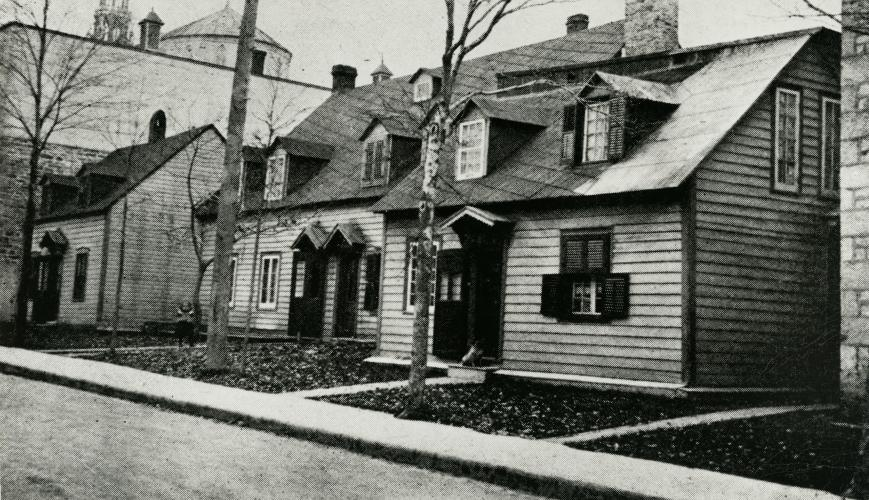 Black and white photograph of three small, wooden, two-storey houses. The houses are very close together, near a large stone religious building.