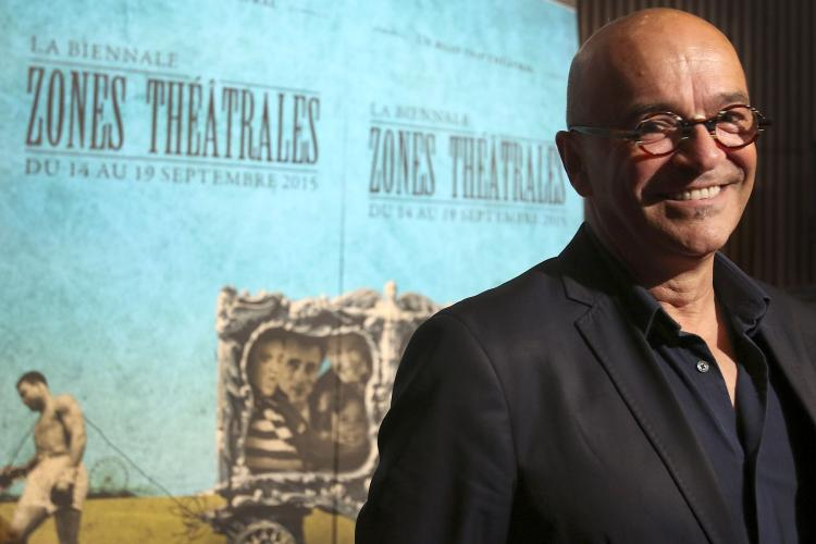 "Colour photograph of a bald, smiling, middle-aged man. He wears glasses and a dark suit. He is standing in front of pale blue posters bearing the words ""LA BIENNALE ZONES THÉÂTRALES DU 14 AU 19 SEPTEMBRE 2015"" (THE BIANNUAL ZONES THÉÂTRALES FROM 14 TO 19 SEPTEMBER 2015."""