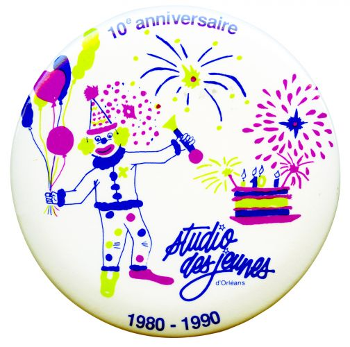 Photograph of a button featuring on white a clown holding balloons, a birthday cake and fireworks in bleu, light green and fuhsia. A blue logo appears on the button as well as an acknowledgement of the anniversary.