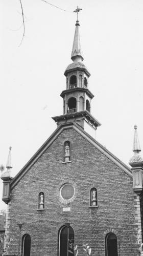Black and white photograph of a brick church, surmounted by a bell tower and two turrets. The facade of the church has three doors, a bull's-eye window, and three statues.