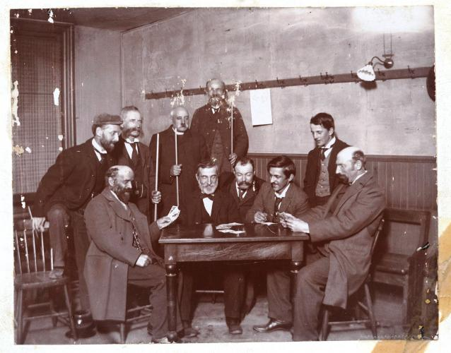 Black and white photograph of a group of men around a table. Five men are seated. Five others, including one cleric, are standing, some holding billiard cues. Two of the seated men hold cards in their hands.
