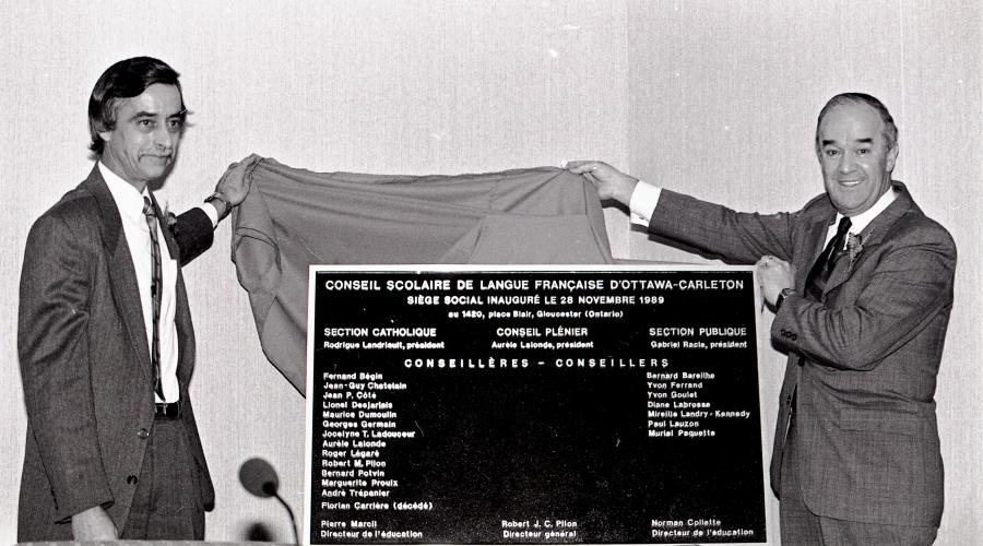 Black and white photograph of two mature men wearing suits and ties. They are smiling as they lift away a cloth to unveil a plaque commemorating the inauguration of the French-language school board. One man looks directly at the camera, while the other looks to one side.
