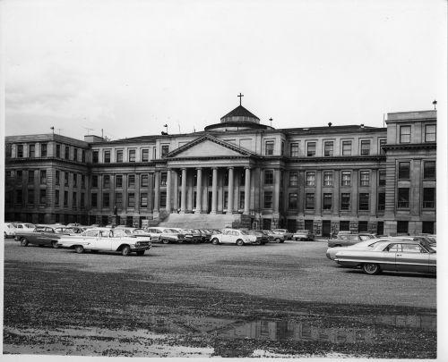 Photographie en noir et blanc d'une cinquantaine de voitures stationnées devant un imposant édifice à quatre étages construit dans le style néoclassique, avec six colonnes ioniques monumentales et un portique à fronton.