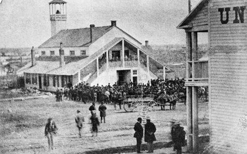 Photographie en noir et blanc d'une foule rassemblée devant un édifice de bois blanc, assez imposant pour l'époque. Le deuxième étage comporte un balcon, auquel on accède par des escaliers extérieurs.