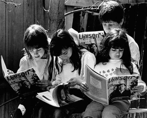 Photographie en noir et blanc d'enfants âgés entre 5 et 10 ans, absorbés dans la lecture du magazine Liaison. Trois fillettes sont assises. Un jeune garçon se tient debout derrière elles.