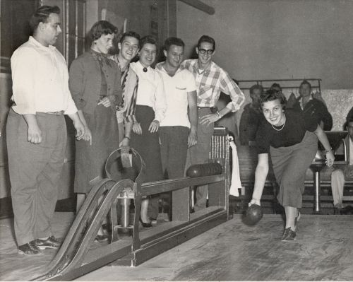 Black and white photograph of young adults playing bowling. They have fun.