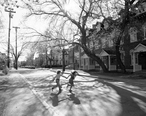 Photographie en noir et blanc de deux enfants qui traversent une rue résidentielle, main dans la main. La rue est bordée de maisons attenantes en briques, à plusieurs étages, et de grands arbres.