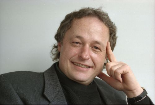 Photographie en couleur d'un homme souriant d'âge moyen, en costume foncé. Il est assis, son index gauche est appuyé contre sa tempe et son pouce gauche, contre sa mâchoire.