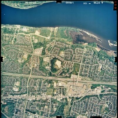 Photographie aérienne en couleur d'un paysage de banlieue où se trouve, au nord (au haut de l'image), une rivière. De nombreuses habitations sont regroupées en lotissements. Une autoroute sépare la zone en deux. On distingue un grand centre commercial au centre de la photo.