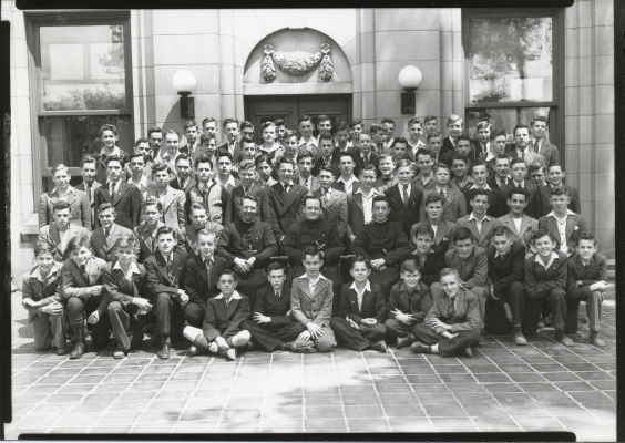 Photographie en noir et blanc d'environ quatre-vingts jeunes garçons, devant un édifice en pierre. Ils sont agenouillés dans la première rangée, assis dans les deux suivantes et debout dans les cinq autres. Tous les garçons portent des costumes et certains portent aussi la cravate. Trois prêtres en soutane sont assis au centre du groupe.