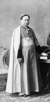 Photographie en noir et blanc d'un homme d'âge mûr portant les vêtements liturgiques d'un archevêque. Ses cheveux bruns courts sont cachés sous sa calotte. Il est debout à côté d'une table, un document dans sa main gauche. Il souffre d'un léger strabisme.