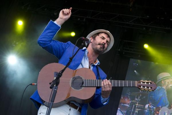 Photographie en couleur d'un homme d'âge moyen, sur une scène. Il porte une barbe courte, noire, un chapeau, un veston bleu royal et un pantalon blanc.  Il joue de la guitare acoustique et chante devant un microphone. Il est photographié en contre-plongée et son image se reflète sur une surface, à sa gauche.