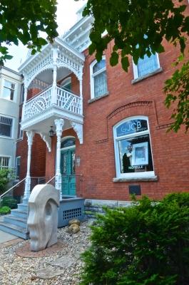 Photographie en couleur d'un édifice en brique à deux étages, prise de biais. La devanture est ornée d'un balcon de bois blanc. Devant l'entrée, une sculpture d'une tête stylisée, de profil. À la fenêtre, un tableau et le nom du commerce, « GJCB Galerie Jean-Claude Bergeron ».