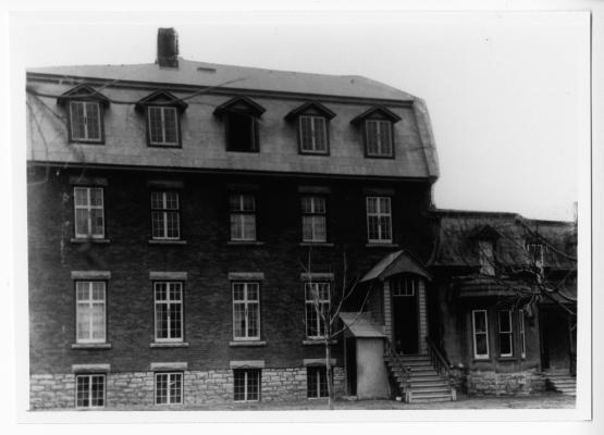 Photographie en noir et blanc d'un édifice en brique de trois étages, à toit mansardé. Un petit escalier mène vers un portique, qui fait office de porte d'entrée. Une maison attenante de plus petite taille le borde à droite.