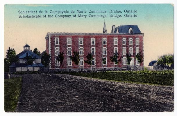 Carte postale en couleur avec texte imprimé, en français et en anglais. Un chemin en terre mène à un édifice en brique de trois étages, surmonté d'un clocher. L'édifice est bordé de petits arbres. D'un côté de l'édifice, une dépendance; de l'autre, une petite maison.