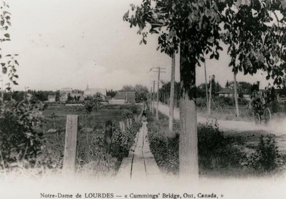 Photographie d'une carte postale en noir et blanc  représentant un chemin de terre menant à une église. On y voit une automobile et une femme. Au bas de la photographie figure un texte dactylographié, en français et en anglais.