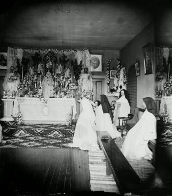 Photographie en noir et blanc d'une novice et de quatre religieuses priant dans une modeste chapelle. L'autel est orné de chandeliers, de fleurs, de statues et d'images saintes.