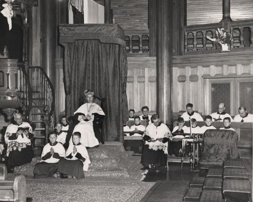 Photographie en noir et blanc d'un religieux d'âge mûr, portant la barrette, assis dans un fauteuil surélevé à côté de la chaire. Il est entouré de cinq autres religieux et de jeunes servants de messe, tous habillés en soutane et en surplis.