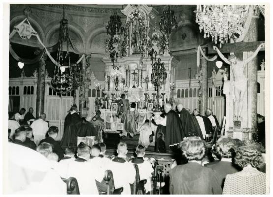 Photographie en noir et blanc de religieux priant à l'autel d'une église. D'autres religieux ainsi que des laïcs assistent à la cérémonie.