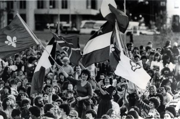 Photographie en noir et blanc d'une foule imposante. Au centre, deux jeunes femmes brandissant des drapeaux ressortent de la foule. D'autres personnes agitent des drapeaux, parmi lesquels on reconnaît deux drapeaux franco-ontariens et un drapeau acadien.