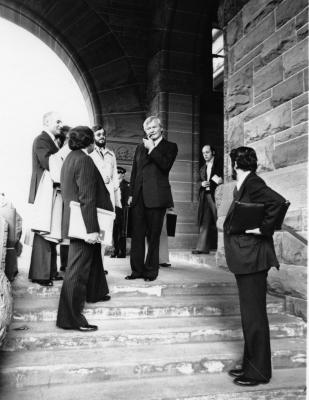 Photographie en noir et blanc d'hommes en costumes foncés, debout sous une arcade de pierre. Les regards convergent vers un homme d'âge mûr qui fume une pipe. Tous tiennent des mallettes et des porte-documents.