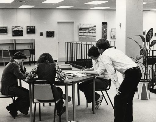Photographie en noir et blanc d'un groupe de deux jeunes femmes et d'un jeune homme, assis autour d'une table dans une salle d'étude. Un adulte, vu de dos, est penché et observe leur travail.