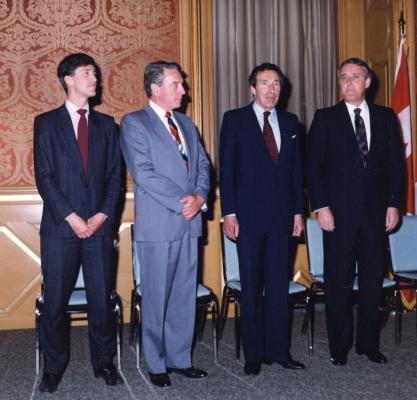 Photographie en couleur d'un jeune homme et de trois hommes d'âge mûr. Tous sont habillés en costume-cravate. Ils sont debout devant des chaises bleues. Un drapeau canadien est visible à l'extrême droite, installé sur une hampe.