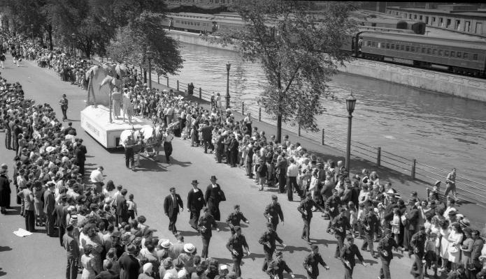 Photographie en noir et blanc d'une foule imposante, le long d'un défilé, au bord d'un canal. Devant un char allégorique tiré par des chevaux défilent des militaires et des religieux. Un train passe sur l'autre rive.