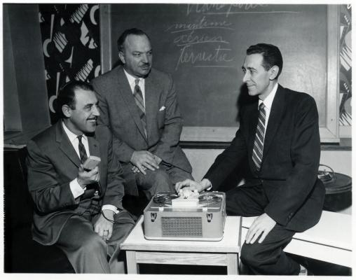 Photographie en noir et blanc de trois hommes d'âge mûr en costumes et cravates. Ils sont assis autour d'un magnétophone à bobines. L'un deux arbore un grand sourire. Derrière eux, un tableau noir.