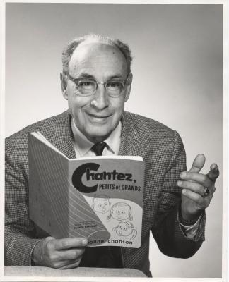 Photographie en noir et blanc, prise en studio, d'un homme d'âge mûr souriant, souffrant de calvitie. L'homme porte des lunettes, un costume à carreaux et une cravate noire. Il tient dans sa main droite un livre, intitulé Chantez, petits et grands.