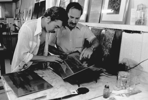 Photographie en noir et blanc d'un homme d'âge moyen et d'un homme d'âge mûr dans un studio d'art. Les deux hommes examinent une œuvre d'art. Plusieurs tableaux sont déposés sur le sol ou accrochés au mur.