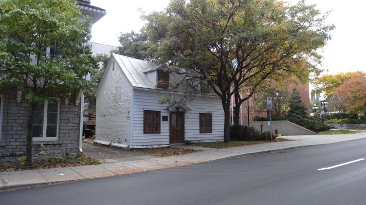 Photographie en couleur d'une maisonnette blanche à deux étages. Un arbre est planté devant la maison.