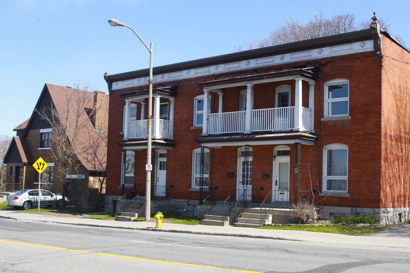 Photographie en couleur d'une maison en rangée à deux étages, à toit plat, en brique. La maison compte trois portes au rez-de-chaussée, surplombées de petits balcons. À sa gauche, une maison individuelle, à deux étages.