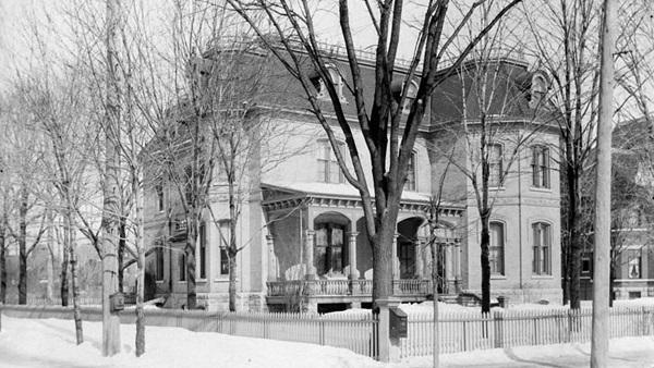 Photographie en noir et blanc d'une maison à trois étages, avec un perron. La maison, vue en hiver, jouit d'une grande cour. Elle est entourée d'une clôture et est bordée d'arbres.