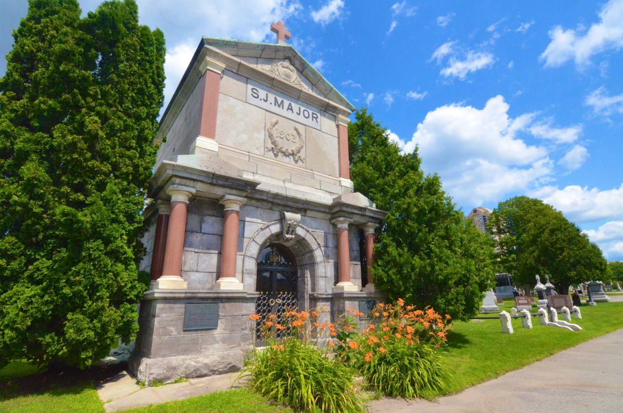 Photographie en couleur d'un très gros monument en pierre, au cœur d'un cimetière. Il est garni de colonnes en marbre et est surmonté d'une croix. Gravée dans la pierre, sur le monument, l'inscription S.J. Major, avec, au bas, 1903.