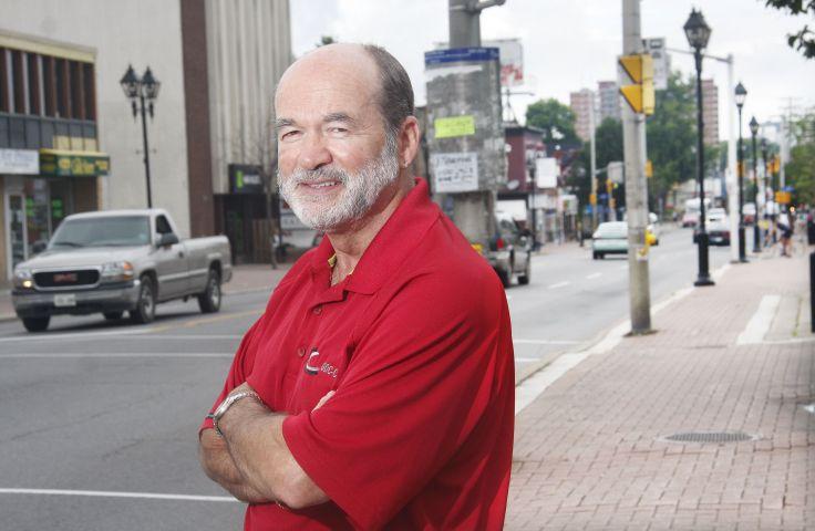 Photographie en couleur d'un homme d'âge mûr. Vêtu d'un polo rouge, les bras croisés, il affiche un air déterminé. Derrière lui, une rue passante de centre-ville.