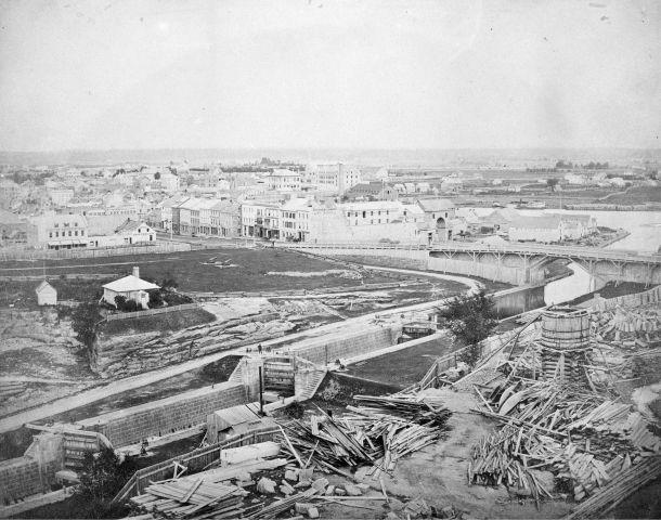 Photographie en noir et blanc d'un canal en pierre avec écluses ; des tas de débris de bois se trouvent sur la rive. En arrière-plan, un pont de bois et un paysage urbain.